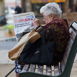 ILLRousse-Corsica-france-elderly-woman-sitting-on-a-bench-reading-the-newspaper